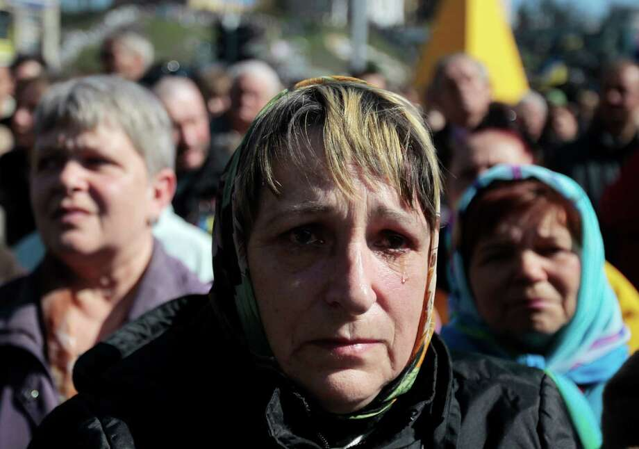 A woman cries during a mourning rally to honor the memory of those who were killed during mass protests in Kiev on Kiev's Independence Square, Sunday, March 30, 2014.  (AP Photo/Sergei Chuzavkov)  ORG XMIT: XSC103 Photo: Sergei Chuzavkov / AP