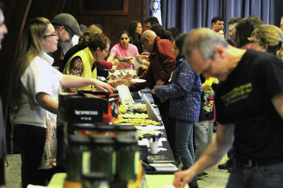Visitors line up to try out different foods at the 11th Annual Jewish Food Festival at the Congregation Gates of Heaven on Sunday, March 30, 2014, in Schenectady, N.Y.  The community festival gives a chance for people to try traditional and modern gourmet Jewish foods prepared by restaurants, caterers, and members of the congregation.   (Paul Buckowski / Times Union) Photo: Paul Buckowski / 00026022A