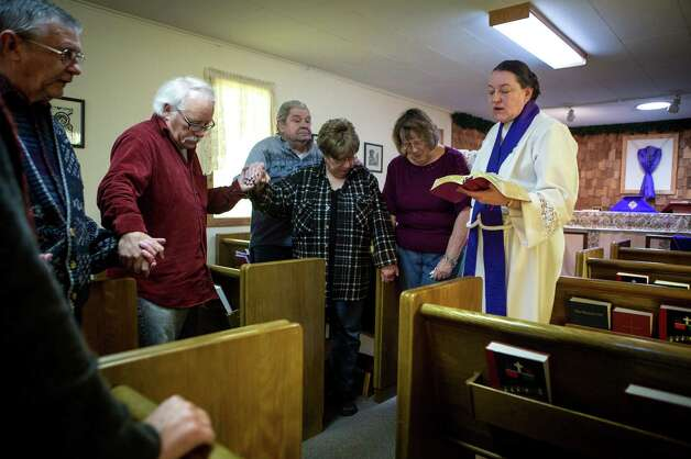 Rev. Janet Loyd, right, prays with members of the Church of the Transfiguration during services in Darrington on Sunday. A significant number of the church members live on the opposite side of the Oso mudslide and were unable to attend the service. More than one week after a deadly mudslide wiped out part of the neighboring community of Oso, area residents gathered to start the healing process. Photo: JOSHUA TRUJILLO, SEATTLEPI.COM / SEATTLEPI.COM