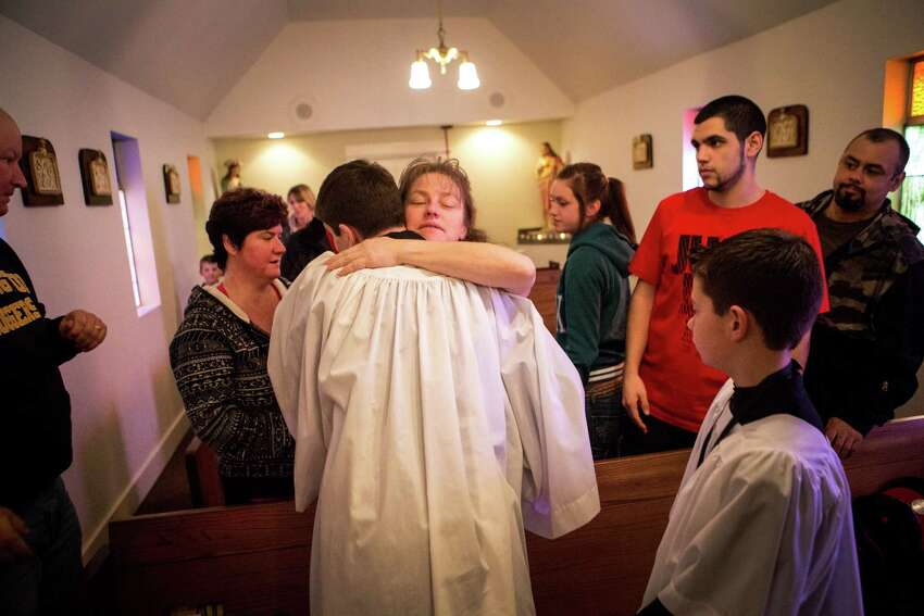 Samantha Valencia, center, hugs her son Felipe Valencia during services at Saint John Vianney Catholic Mission in Darrington. The pastor, Rev. Tim Sauer, also preaches at Immaculate Conception in Arlington and had to adjust the Sunday schedule to accommodate the two hour drive around the Oso mudslide. Sauer has helped with efforts to pay funeral expenses for all victims of the Oso mudslide, regardless of denomination or religious belief.