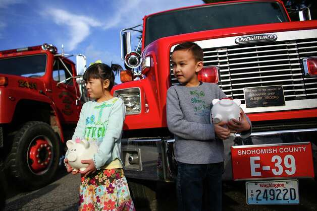 "Anya Lin, 6, and Talon, 7, of Darrington bring their piggy banks to the Darrington Fire Department to donate to rescue workers on Sunday. The kids said it was ""their college savings"" but they wanted to give it to those working in the muddy mess. The money will likely go to new boots for the loggers volunteering in the mudslide mess. The donation brought smiles to weary rescue workers and others dealing with the tragedy. Photo: JOSHUA TRUJILLO, SEATTLEPI.COM / SEATTLEPI.COM"
