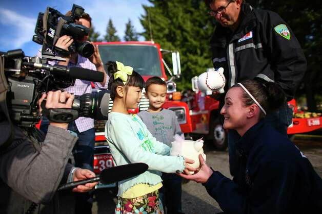 Anya Lin, 6, and her brother Talon, 7, present their piggy banks to Gabby Kernaghan and Jeff McClelland at the Darrington Fire Department on Sunday, March 30, 2014. More than one week after a deadly mudslide wiped out part of the neighboring community of Oso, area residents gathered at churches and community centers to start the healing process. Photo: JOSHUA TRUJILLO, SEATTLEPI.COM / SEATTLEPI.COM