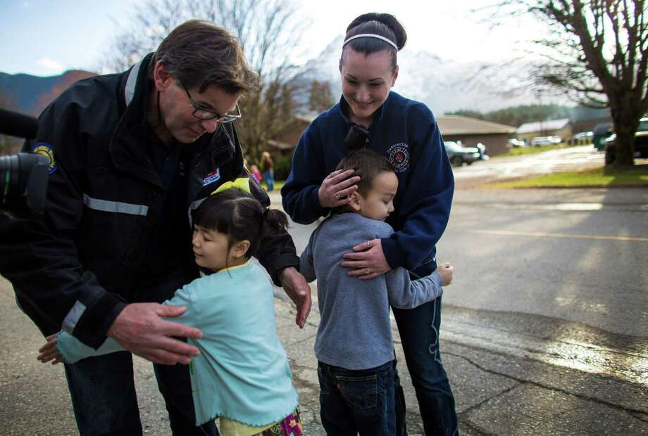 """Anya Lin, 6, and her brother Talon, 7, present their piggy banks to firefighters Jeff McClelland and Gabby Kernaghan and at the Darrington Fire Department. The kids said it was """"their college savings"""" but they wanted to give it  to those working in the muddy mess. The money will likely go to new  boots for the loggers volunteering in the mudslide mess. The donation brought smiles to weary rescue workers and others dealing with the tragedy. Photo: JOSHUA TRUJILLO, SEATTLEPI.COM / SEATTLEPI.COM"""