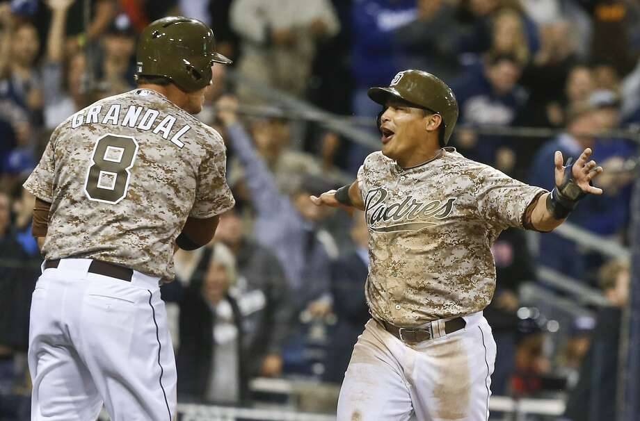 San Diego Padres' Everth Cabrera celebrates with Yasmani Grandal after the pair scored in the eighth against the Los Angeles Dodgers in the opening game of Major League baseball in the United States Sunday, March 30, 2014, in San Diego.  (AP Photo/Lenny Ignelzi) Photo: Lenny Ignelzi, Associated Press