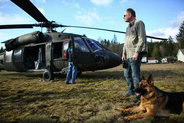 Arlington City Councilmember Chris Raezer stands with his dog Hansel alongside a Washington National Guard UH-60 Black Hawk that landed in downtown Darrington. The city councilor said he wanted to check on his neighbors to the east and made the long drive around the mudslide to see how Darrington was dealing with the tragedy. Photo: JOSHUA TRUJILLO, SEATTLEPI.COM / SEATTLEPI.COM