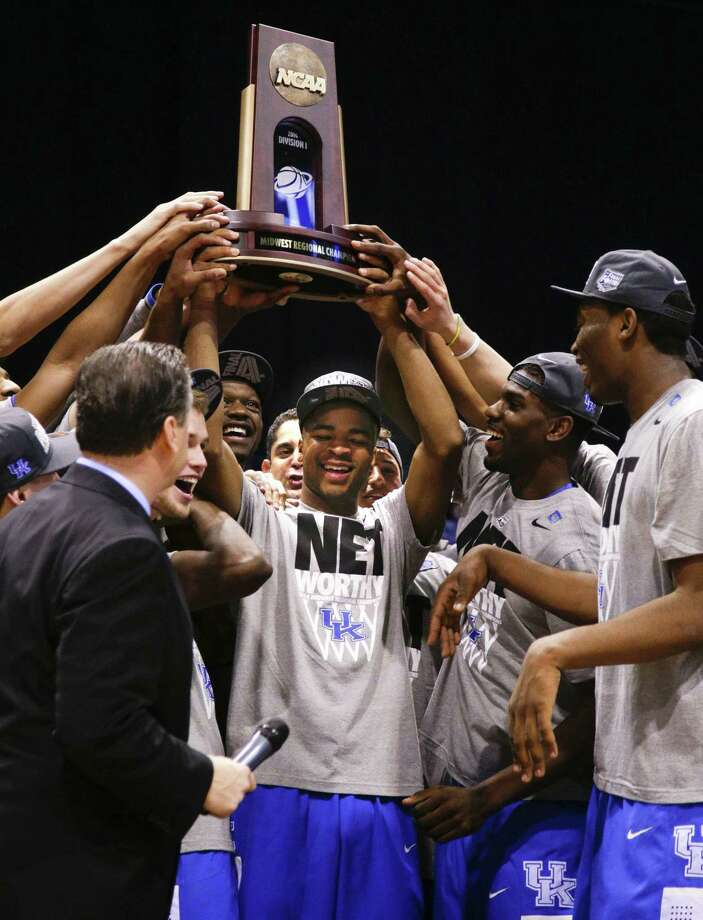 Kentucky freshman guard Aaron Harrison (center), who hit the game-winner, and his teammates display their Midwest Region trophy. Photo: Mark Cornelison / McClatchy-Tribune / Lexington Herald-Leader