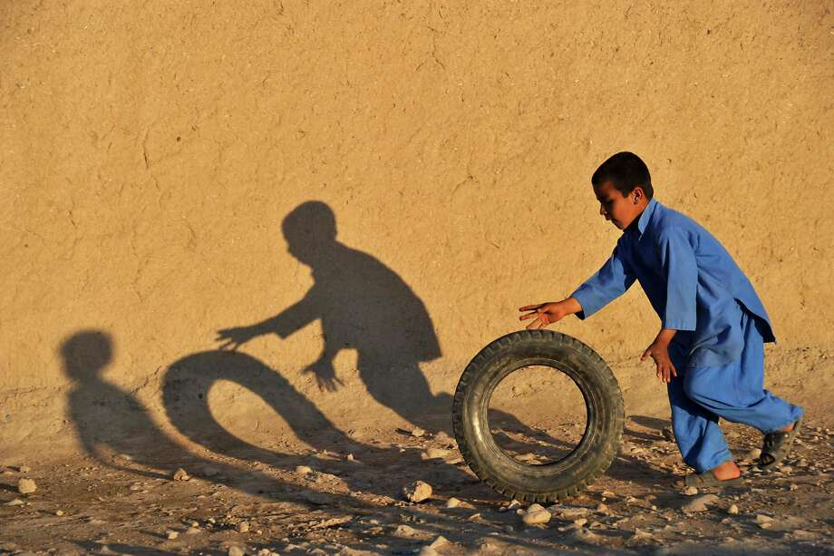An Afghan child plays with a tire along a street in a village on the outskirts of Jalalabad on March 30, 2014. The literacy rate in Afghanistan is about 30 percent and about 42 percent of the country's population is under the age of 14. According to UNICEF more boys than girls attend classes in primary school in Afghanistan. AFP PHOTO/NOORULLAH SHIRZADANoorullah Shirzada/AFP/Getty Images Photo: Noorullah Shirzada, AFP/Getty Images