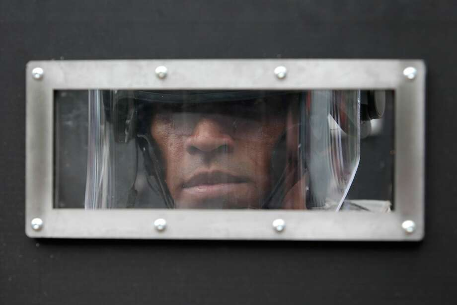 A police officer from the Brazilian National Force peers through his shield as he trains during a simulated protest in preparation for World Cup security in Brasilia, Brazil, Sunday, March 30, 2014. Brazil will host the soccer tournament starting in June. (AP Photo/Eraldo Peres) Photo: Eraldo Peres, Associated Press