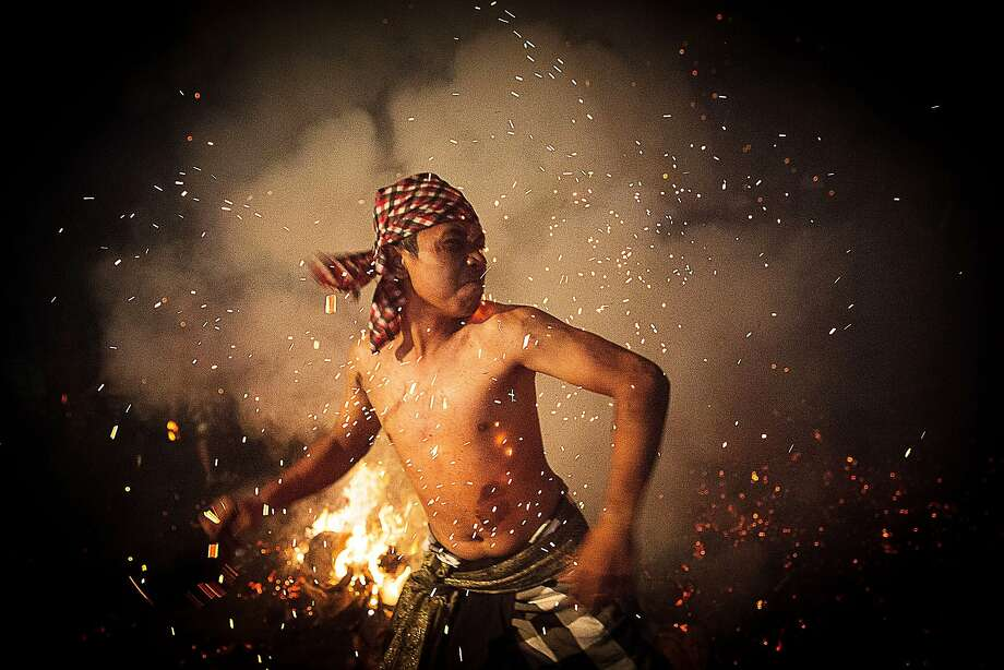 "GIANYAR, BALI, INDONESIA - MARCH 30:  A Balinese man throws a burned coconut husk during the ""Mesabatan Api"" ritual a head of Nyepi Day on March 30, 2014 in Gianyar, Bali, Indonesia. Mesabatan Api is held annually a day before the Nyepi Day of Silence, as symbolizes the purification of universe and human body trough fire. Nyepi is a Hindu celebration observed every new year according to the Balinese calendar. The national holiday is one of self-reflection and meditation and activities such as working, watching television or travelling are restricted between the hours of 6 a.m. and 6 p.m.  (Photo by Agung Parameswara/Getty Images) *** BESTPIX *** Photo: Agung Parameswara, Getty Images"