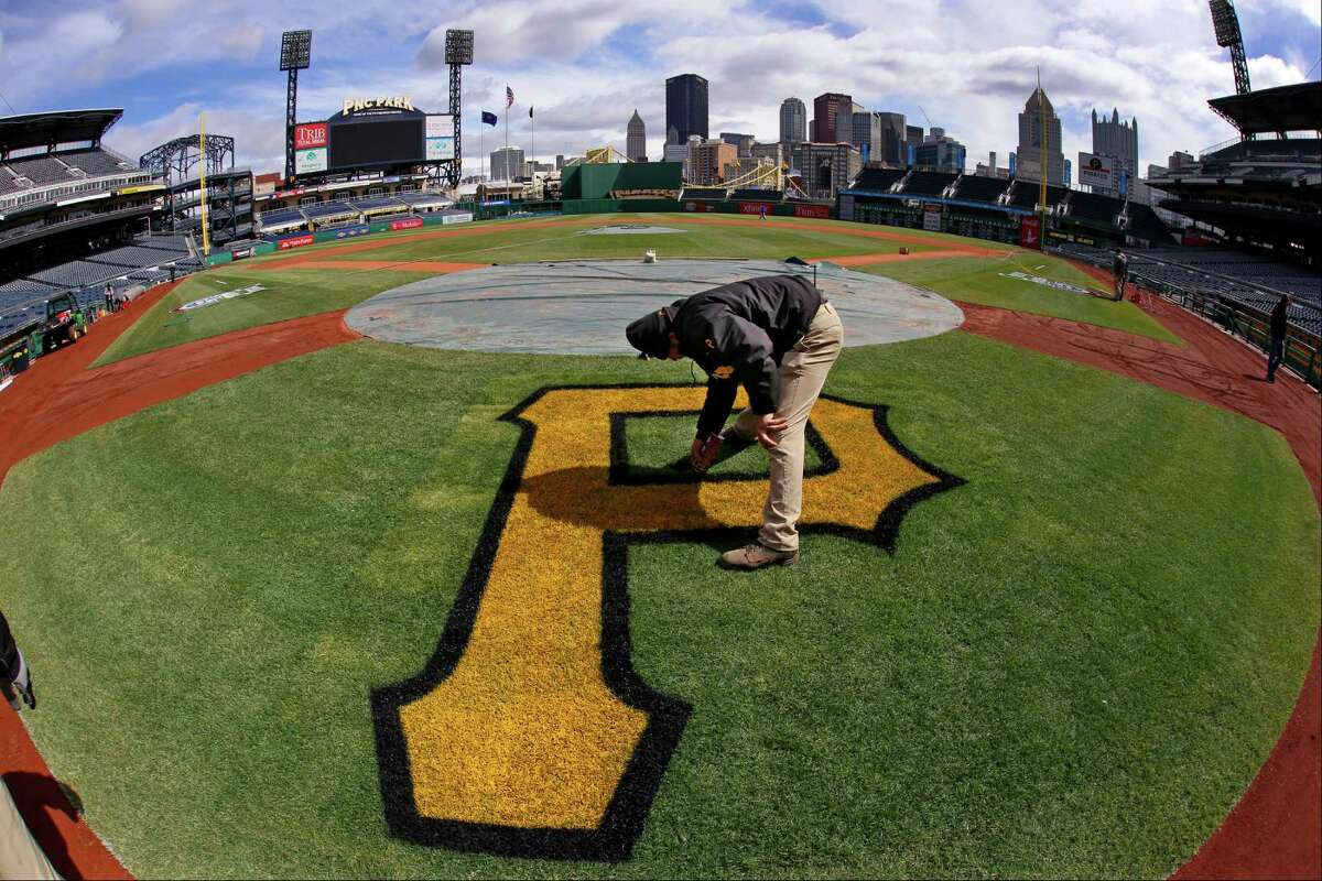 In this photo made with a fisheye lens, Derek Hurlburt, assistant field management supervisor at PNC Park, puts the finishing touches on the Pittsburgh Pirates logo behind home plate Sunday, March 30, 2014, in preparation for the Pittsburgh Pirates season opening baseball game, Monday, March 31 against the Chicago Cubs in Pittsburgh. (AP Photo/Gene J. Puskar) ORG XMIT: PAGP102