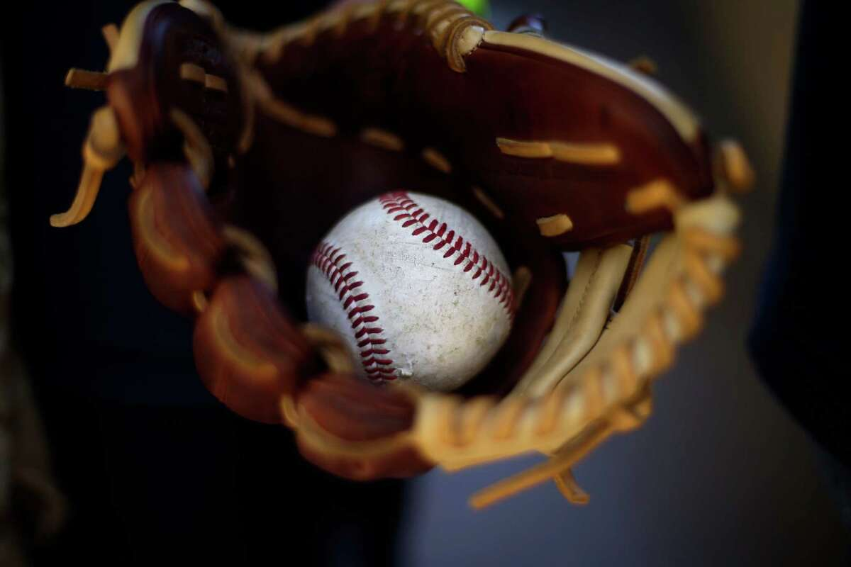 Peyton Berroth carries a baseball in his glove as he arrives to Petco Stadium before an opening day baseball game between the Los Angeles Dodgers and the San Diego Padres on Sunday, March 30, 2014, in San Diego. (AP Photo/Gregory Bull) ORG XMIT: CAGB106