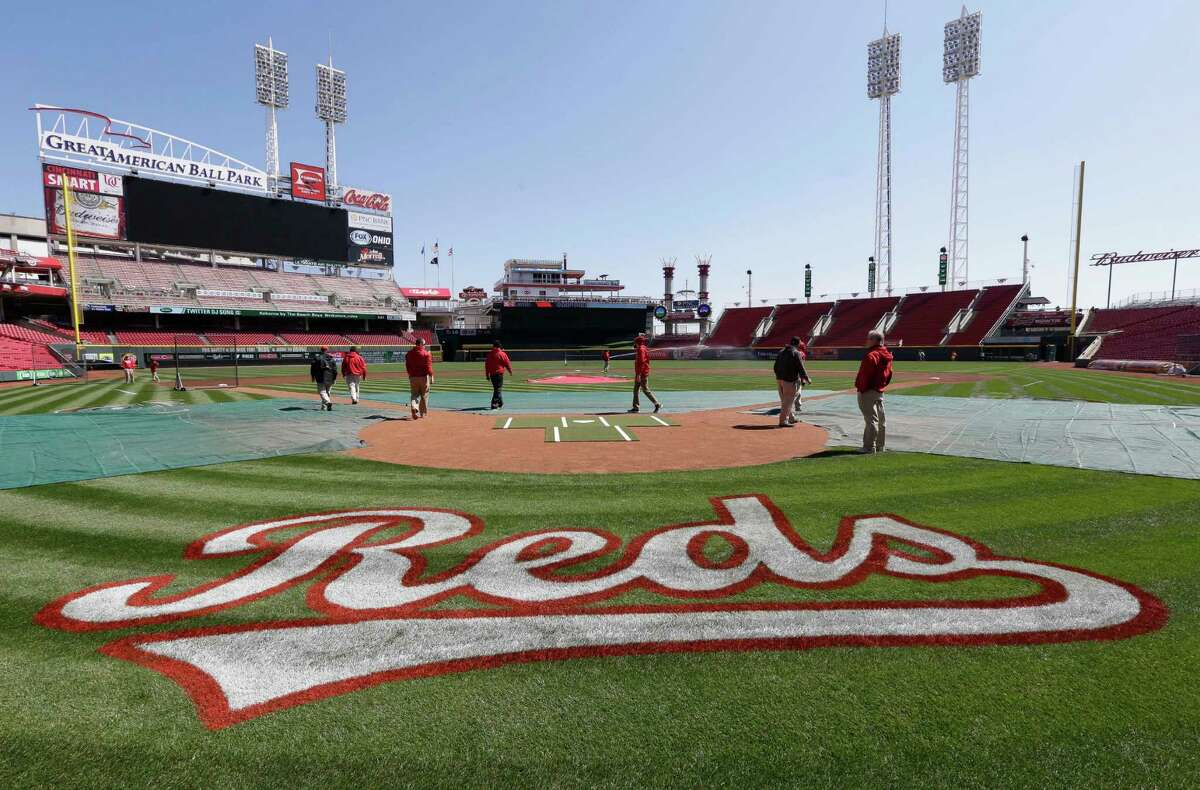 The Cincinnati Reds grounds crew checks the field on Sunday, March 30, 2014, in Cincinnati. The Reds host the St. Louis Cardinals, Monday afternoon in their Opening Day baseball game. (AP Photo/Al Behrman) ORG XMIT: OHAB106