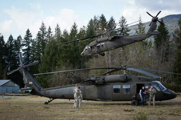 A Washington National Guard UH-60 Blackhawk helicopter lifts off from a field in downtown Darrinton on Sunday, March 30, 2014. More than one week after a deadly mudslide wiped out part of the neighboring community of Oso, area residents gathered at churches and community centers to start the healing process. Photo: JOSHUA TRUJILLO, SEATTLEPI.COM / SEATTLEPI.COM