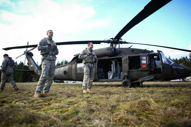 Members of the Washington National Guard stand around their UH-60 Blackhawk helicopter in a field in downtown Darrington. Photo: JOSHUA TRUJILLO, SEATTLEPI.COM / SEATTLEPI.COM