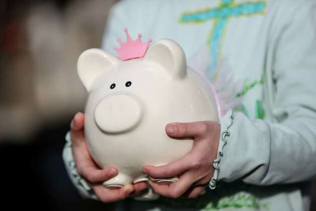 "Anya Lin, 6, holds onto the piggy bank she donated to the Darrington Fire Department. The kids said it was ""their college savings"" but they wanted to give it to those working in the muddy mess. Photo: JOSHUA TRUJILLO, SEATTLEPI.COM / SEATTLEPI.COM"