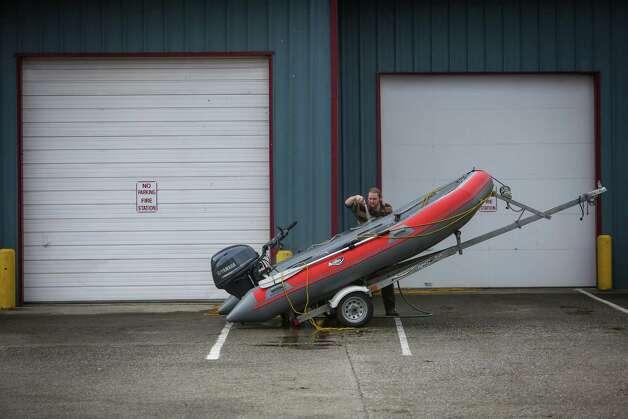 A volunteer hoses off a rescue boat at the Darrington, Wash. Fire Station. Photo: JOSHUA TRUJILLO, SEATTLEPI.COM / SEATTLEPI.COM