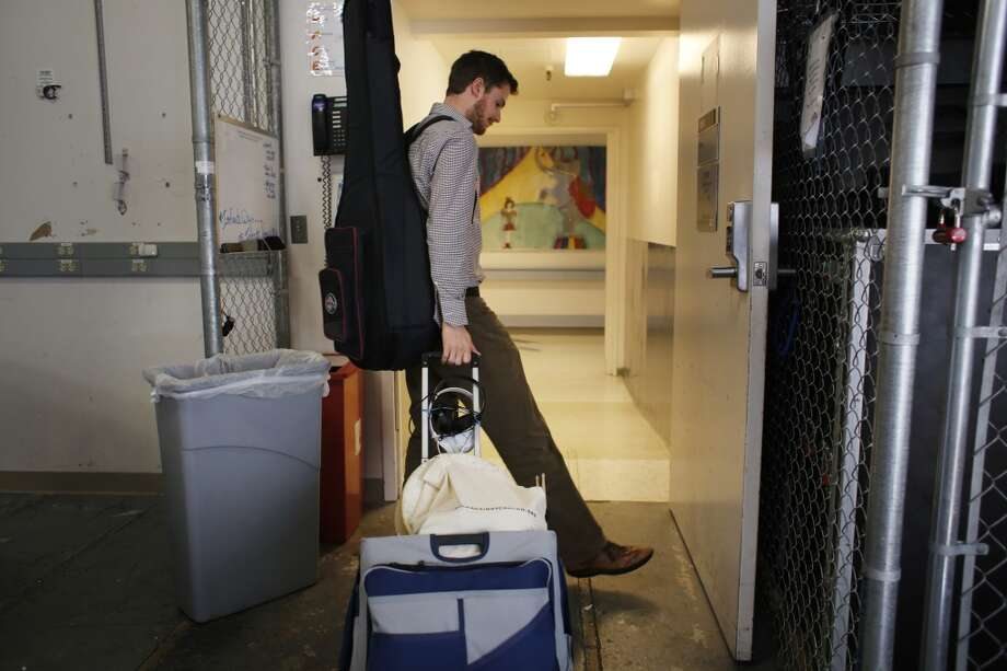 Oliver Jacobson, music therapist at UCSF Benioff Children's Hospital, wheels his cart out of storage at the start of his afternoon shift on Wednesday March 26, 2014 in San Francisco, Calif. Photo: Mike Kepka, The Chronicle