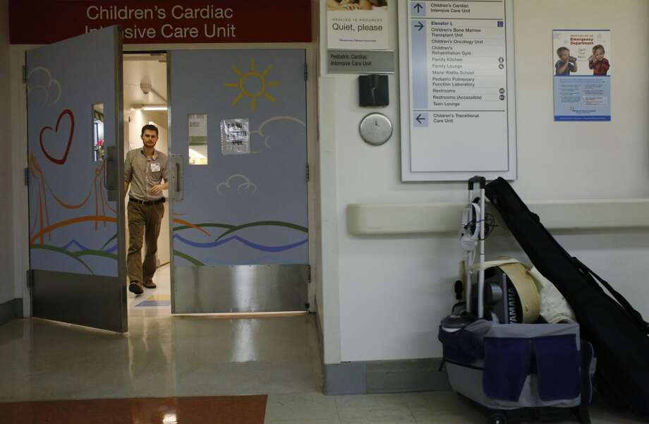 Oliver Jacobson, music therapist at UCSF Benioff Children's Hospital, checks on a patient in the Children's Cardiac ICU on Wednesday March 26, 2014 in San Francisco, Calif. Photo: Mike Kepka, The Chronicle