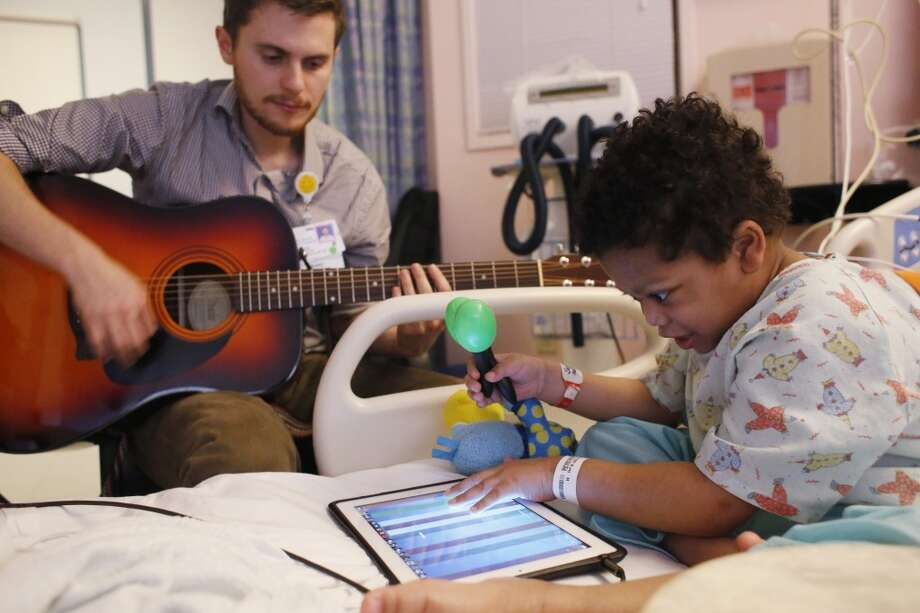On the last day of a 2 month hospital stay, Mickey Sellu, 6, jams with Oliver Jacobson, music therapist at UCSF Benioff Children's Hospital, on Wednesday March 26, 2014 in San Francisco, Calif. Photo: Mike Kepka, The Chronicle