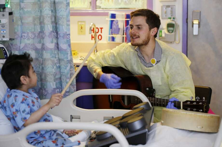 Oliver Jacobson, music therapist at UCSF Benioff Children's Hospital, works with Julian Barajas, 9, during a therapy session on Wednesday March 26, 2014 in San Francisco, Calif. Photo: Mike Kepka, The Chronicle