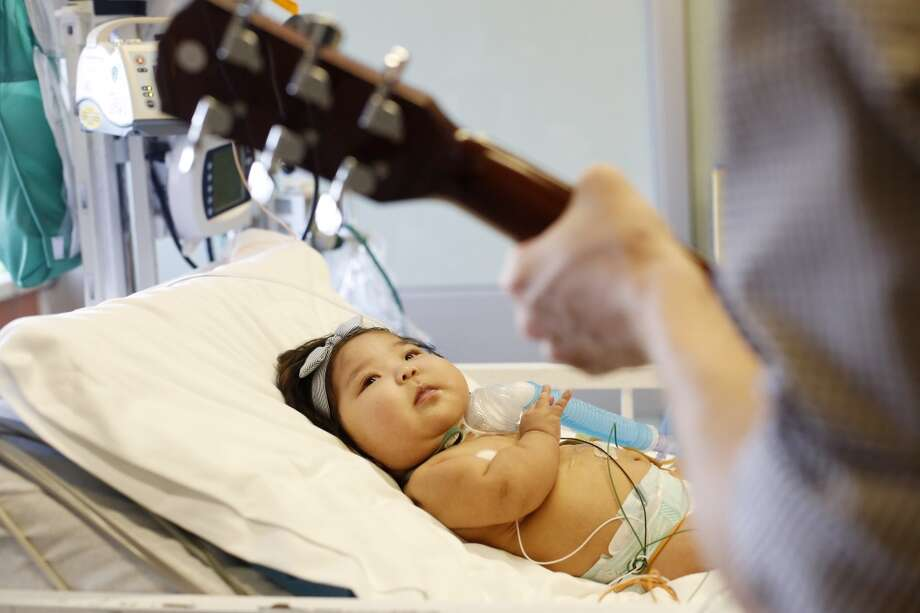 Oliver Jacobson, music therapist at UCSF Benioff Children's Hospital, sing lullabies to Maia Mead, 7-months, as she keeps and eye on his guitar in the pediatric cardiac ICU on Wednesday March 26, 2014 in San Francisco, Calif. Photo: Mike Kepka, The Chronicle