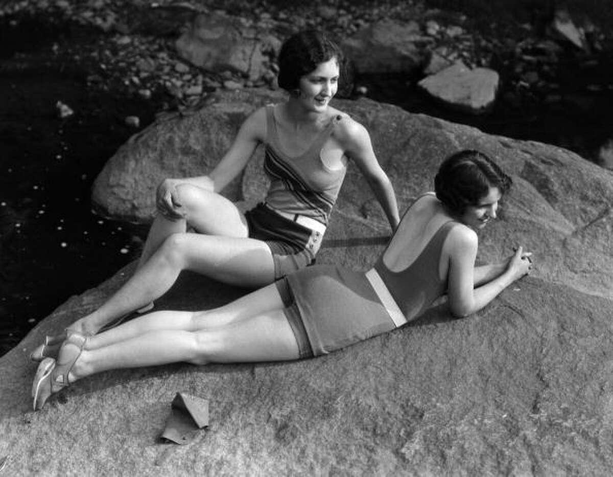 1920s: Two women relaxing on rock, by creek.