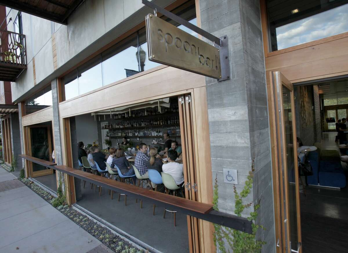The front entrance to Spoonbar overflows with guests onto Healdsburg Avenue during warm summer nights.
