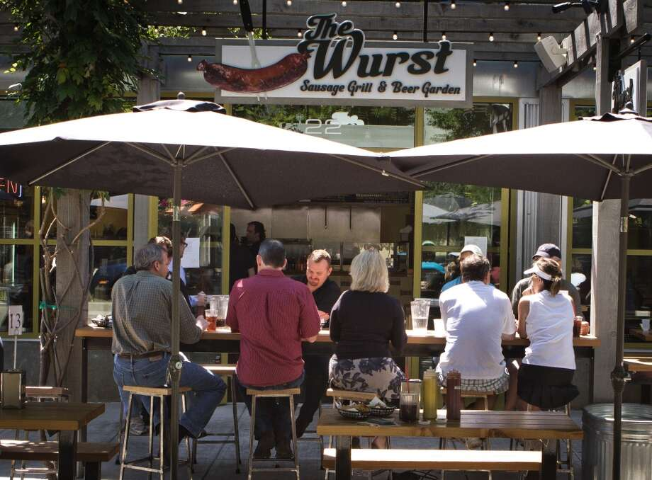 Diners enjoy lunch outside at the Wurst Sausage Grill and Beer Garden, a casual spot just off the downtown square. Photo: John Storey, Special To The Chronicle