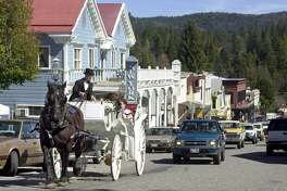 NEVADA CITY : Old and new cross paths as cars follow behind a horse drawn carriage tour through Nevada City.  ( Drive time: 2.5 hours )