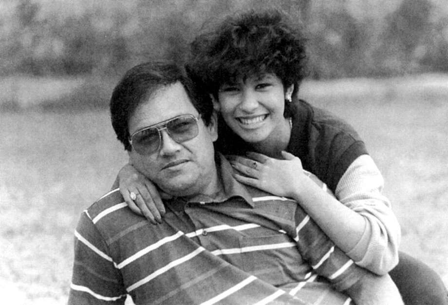 Fourteen-year-old Selena poses with her father, Abraham, in the Corpus Christi backyard of Rosalia Hernandez, the photographer's mother. The occasion was Selena's first photo shoot for publicity stills.