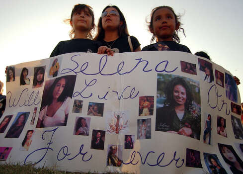 Kateri Lopez, 8, (from left) Julie Castillo, and Alexis Castillo, 7, hold a poster with photos of slain Tejano star Selena during a tribute Thursday March 31, 2005 at Cole Park in Corpus Christi. / SAN ANTONIO EXPRESS-NEWS