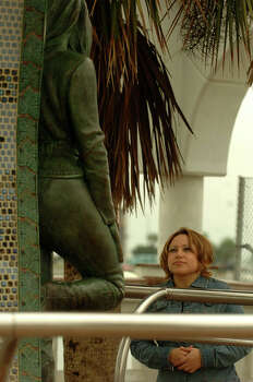 Jackie Lizama, of Nacogdoches, Texas, pays her respects at the Selena memorial in Corpus Christi, Texas, on Thursday, March 3, 2005. Selena Quintanilla-Perez, a rising star and popular singer from Corpus Christi,  was shot to death 15 years ago. Lizama has unused tickets to a concert which Selena was to perform in Tyler, Texas. Selena died before the concert took place. / SAN ANTONIO EXPRESS-NEWS