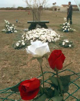 Visitors to the grave of slain Tejano music star Selena leave various gifts including roses, shown hanging on the fence surrounding her grave, Sunday, March 31, 1996, in Corpus Christi. / AP1996