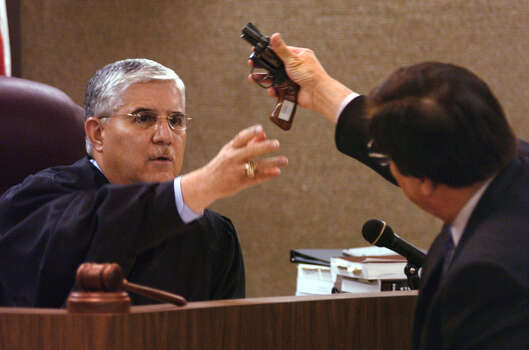 Capt. Paul Rivera, right, of the Nueces County Sheriff's Department, hands the .38-caliber revolver used to kill singer Selena to Judge Jose Longoria, Thursday, June 6, 2002, in Corpus Christi, Texas. Longoria ruled that the gun be handed over to the county sheriff's office to be destroyed. Sheriff Larry Olivarez was present in the courtroom and took possession on the gun. / CORPUS CHRISTI CALLER-TIMES