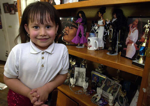 "Selena Guitron, 4, poses by a cabinet full of ""Selena"" memorabilia at her house on Aldama Street. She was named after the late Tejano singer. / EN"