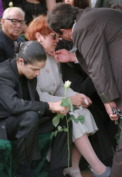 Father of slain Tejano music star, Abraham Quintanilla, right, consoles his wife, Marcella, as Chris Perez, husband of Selena, bows his head during funeral services Monday, April 3, 1995, in Corpus Christi. / POOL AP
