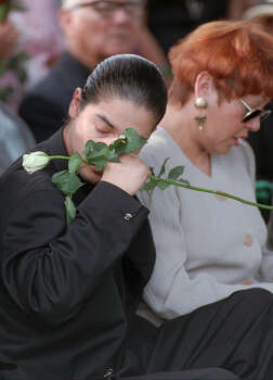 Chris Perez, the husband of slain Tejano star Selena, wipes a tear away from his eye during her funeral in Corpus Christi April 3, 1995. Next to him his Selena's mother, Marcella Quintanilla. / AP
