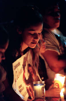 Patricia Hernandez bows her head during a candlelight vigil on April 1, 1996, in honor of slain Tejano singer Selena Sunday evening in Corpus Christi on the anniversary of her death.  A grassroots effort brought about the vigil at a local neighborhood grocery store two blocks from Selena's house.