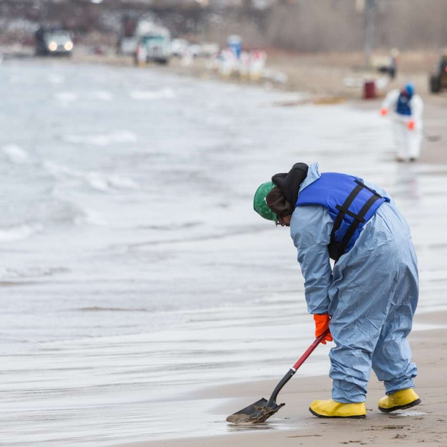 In this March 25, 2014 photo, a worker collects soil from the beach in Whiting, Ind. Crews for oil giant BP worked Tuesday to clean up an undetermined amount of crude oil that spilled into Lake Michigan and affected about a half-mile section of shoreline near Chicago following a malfunction at BP's northwestern Indiana refinery, officials said. Photo: Jim Karczewski, AP