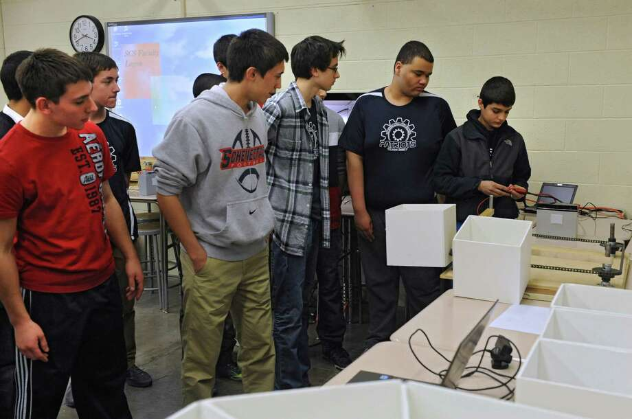 "Members of the ""Retrievers"" team demonstrate part of the mechanism for the robot they are constructing for competing in the NASA Sample Return Robot Centennial Challenge at Schenectady High School Monday, March 24, 2014 in Schenectady, N.Y. The SHS team is competing for the $1.5 million prize with teams from as far as Canada, California and Estonia, demonstrating robots that Ocan navigate a complex terrain while seeking out samples that they must return to a designated point in a set period of time,O according to WPI. (Lori Van Buren / Times Union) Photo: Lori Van Buren / 00026249A"