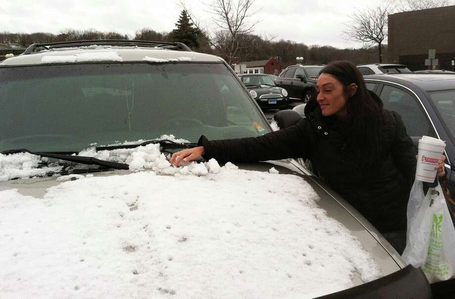 A surprise spring snowfall Monday morning had people like Christina Voight scraping the wet snowfall off her windshield in a downtown parking lot. Photo: Jarret Liotta / Westport News