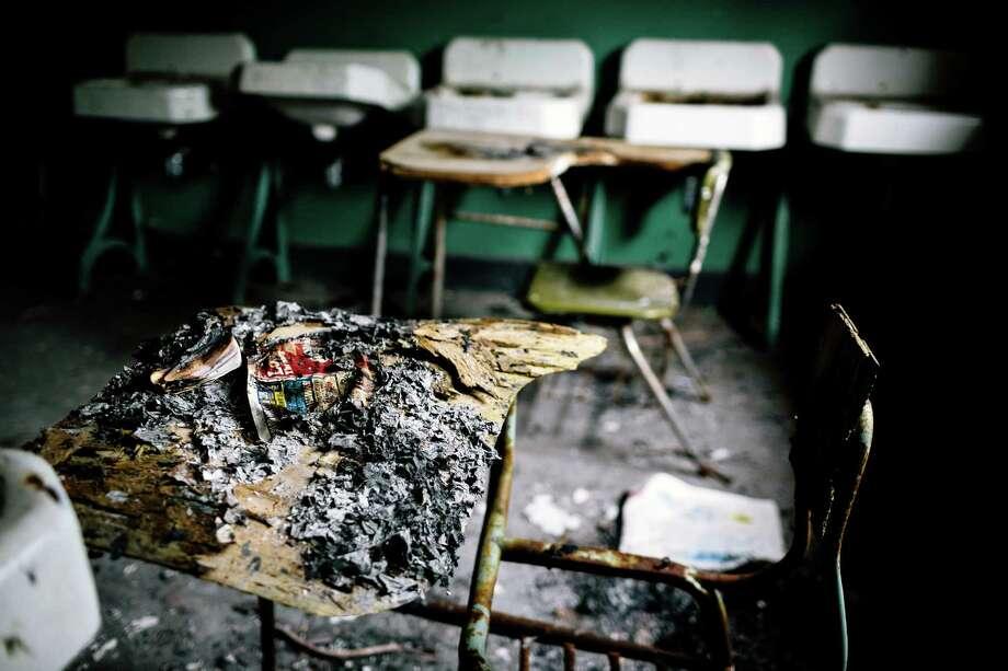 Burned, tattered newspapers pile up on a desk within a former Nike Site S-13/14 missile site. Photo: JORDAN STEAD, SEATTLEPI.COM / SEATTLEPI.COM