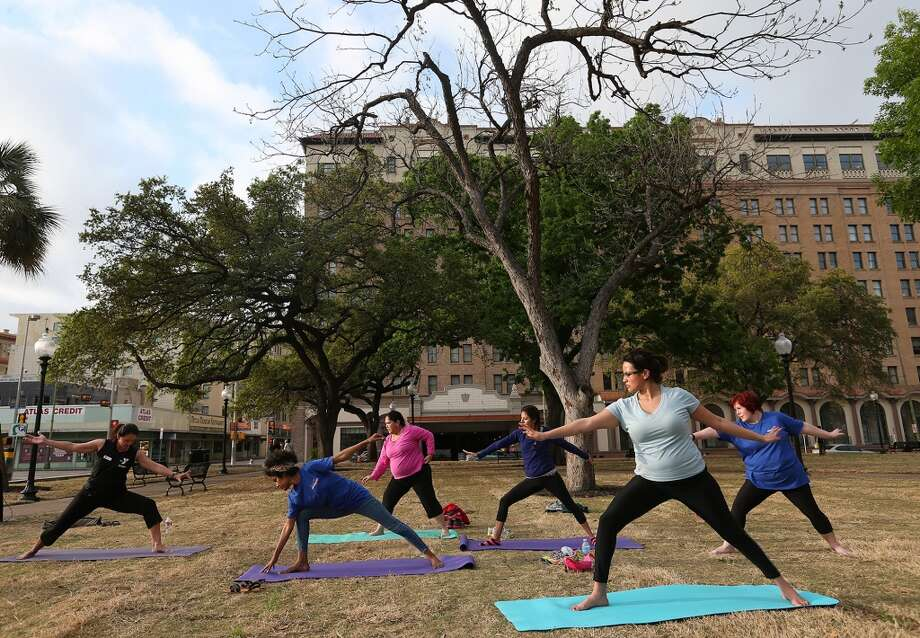 Women participate in the YMCA Yoga in the Park during the City of San Antonio's reopening of Travis Park with events on Monday, March 31, 2014. The 2.6-acre park was closes in January for the rennovation. Exercise classes will be held at the park on a regular basis. Photo: JERRY LARA, San Antonio Express-News