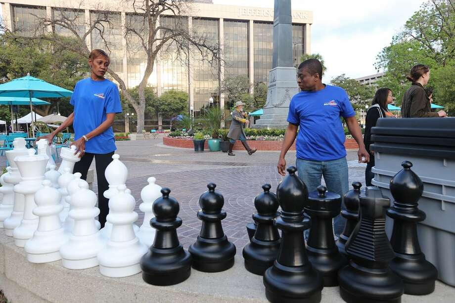 Southwest Airllines employees Loretta Bailey, left, and Wildor Saint Fort help set up an oversized chess game for the City of San Antonio reopening of Travis Park ceremony, Monday, March 31, 2014. Photo: JERRY LARA, San Antonio Express-News