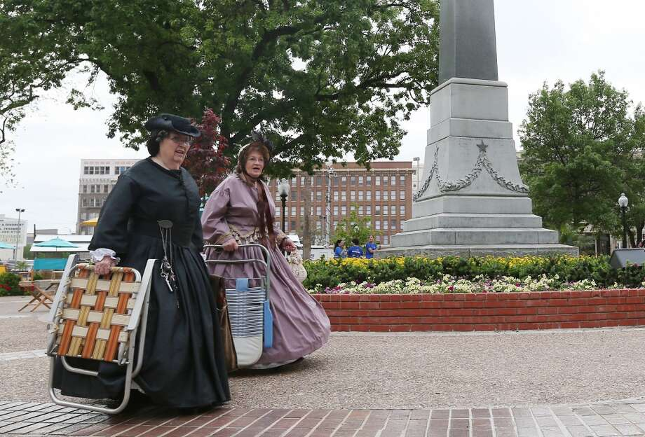Dressed in period costumes, Eileen Lehmberg, left, and Loretta Smith arrvie for the City of San Antonio reopening of Travis Park celebration, Monday, March 31, 2014. Photo: JERRY LARA, San Antonio Express-News