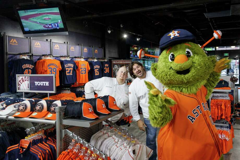 Chefs Dominic Soucie, left, and Bryan Caswell joke around with Orbit, the Houston Astros mascot, in the newly revamped Majestic Team Store at Minute Maid Park. Caswell and chef Ronnie Killen are collaborating on a new stand at the park, Texas Smoke. Photo: Michael Paulsen, Staff / © 2014 Houston Chronicle
