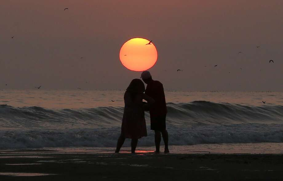 Some enchanted evening: A couple watch the sun set on Sarapampa beach in Lima, Peru. Photo: Martin Mejia, Associated Press
