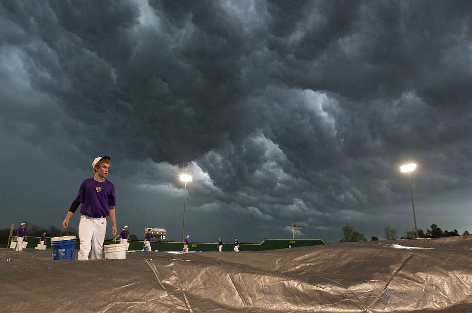 Angry skies:Greg Swanson helps his teammates tarp a baseball field as thunderstorms approach in   Montgomery, Texas. Photo: Jason Fochtman, Associated Press