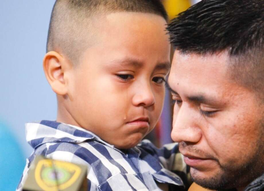 A tear rolls down the cheek of Jonathan Chamorro, 5, held by father German Chamorro during a Monday news conference about the death of Maria Lucrecia, 27, a pregnant cleaning woman at Eclipse Gentlemen's Club. Osvaldo Fernandez-Aguilar, who worked security at the club, is charged with capital murder in her death. Photo: Cody Duty, Houston Chronicle