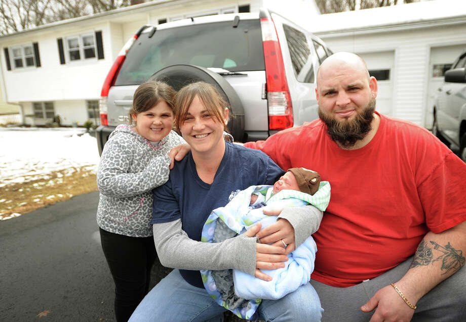 Jennifer Scollin and Matthew Dillman with their children Kelsey Dillman, 4, and newborn Cole Dillman outside their Tracy Terrace home in Seymour, Conn. on Monday, March 31, 2014. Scollin, who says she didn't know she was pregnant, gave birth to the nine pound Cole in an ambulance in her driveway on Saturday morning. Photo: Brian A. Pounds / Connecticut Post